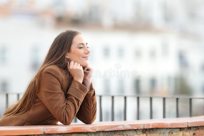 Satisfied woman heating in winter closing eyes in a balcony. Side view portrait of a satisfied woman wearing jacket heating in winter with closed eyes in a stock photos