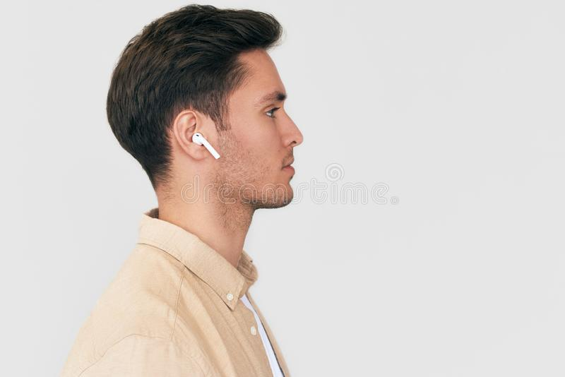 Side view portrait of serious young handsome man posing with wireless earphones on white studio background. Caucasian businessman stock images