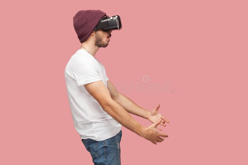 Side view portrait of shocked bearded young man in white shirt, casual hat standing, wearing vr, playing video game and trying to stock photography