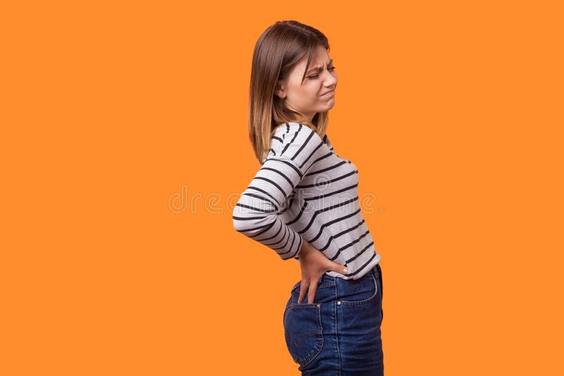 Side view portrait of sick woman with brown hair in long sleeve striped shirt standing with grimace of pain. indoor studio shot. Side view portrait of sick woman stock photo