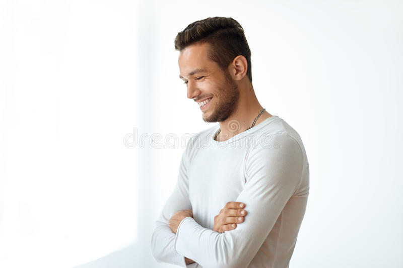 Side view portrait of smiling handsome man on white background royalty free stock image