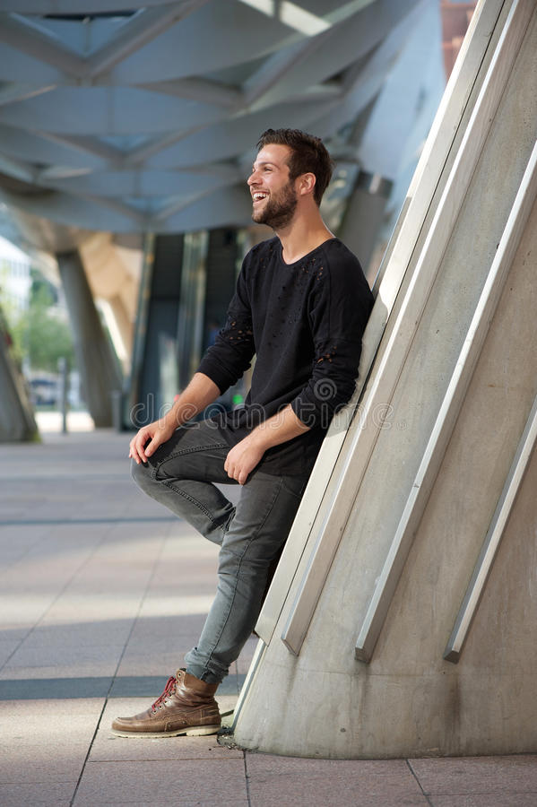 Side view portrait of smiling man standing outdoors. Full length side view portrait of smiling man standing outdoors royalty free stock images