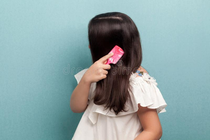 Side view portrait of teenager girl in white dress standing, making attention and combing brunette hair with pink hairbrush. royalty free stock photo