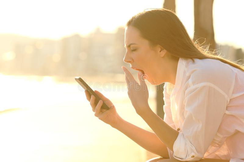 Tired woman using phone yawning on the beach royalty free stock photo