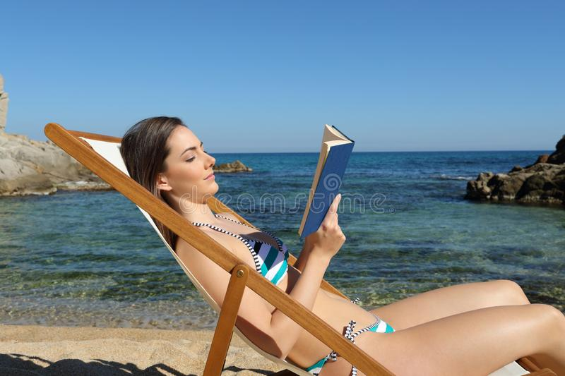 Tourist reading a book on a hammock on the beach. Side view portrait of a tourist reading a book on a hammock on the beach on summer vacation royalty free stock photo