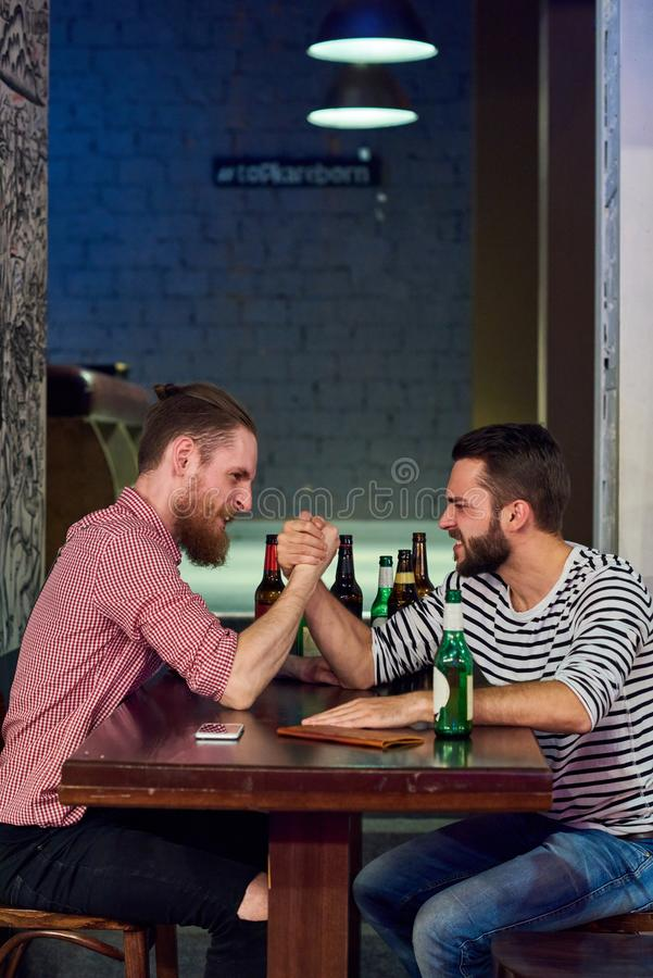 Two Men Armwrestling in Bar. Side view portrait of two modern young men armwrestling sitting at table in bar and drinking beer, copy space royalty free stock image