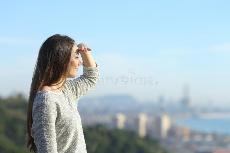 Woman looking away protecting sight with hand. Side view portrait of a woman looking away protecting from the sun with hand stock photos