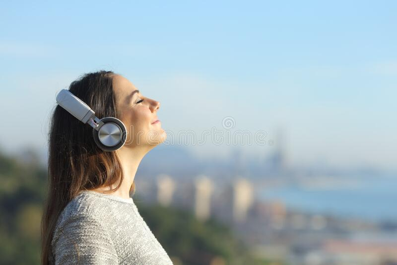 Woman listening to music breathing outdoors royalty free stock photo