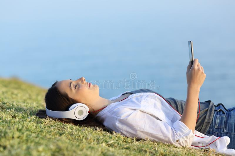Woman relaxing listening to music on the grass stock image
