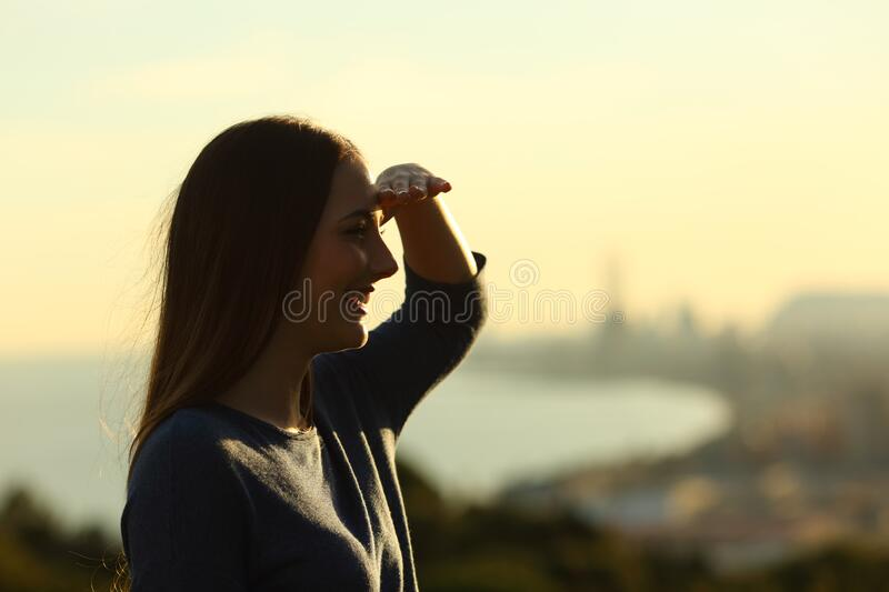 Woman silhouette protecting from sun with hand. Side view portrait of a woman silhouette protecting from sun with hand at sunset stock image
