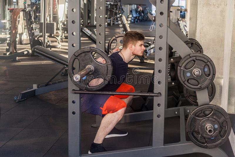 Side view portrait of young adult bodybuilder are workout in gym alone and prepearing to lifting barbell, doing exercises for legs. Indoor, looking away royalty free stock photos