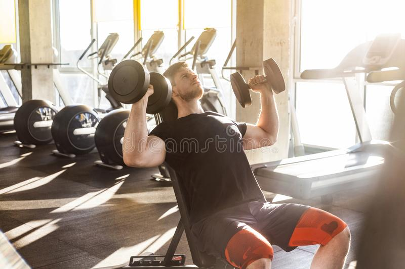 Side view portrait of young adult sport man training at gym alone. Athlete workout in gym, sitting and holding two dumbbell with royalty free stock images