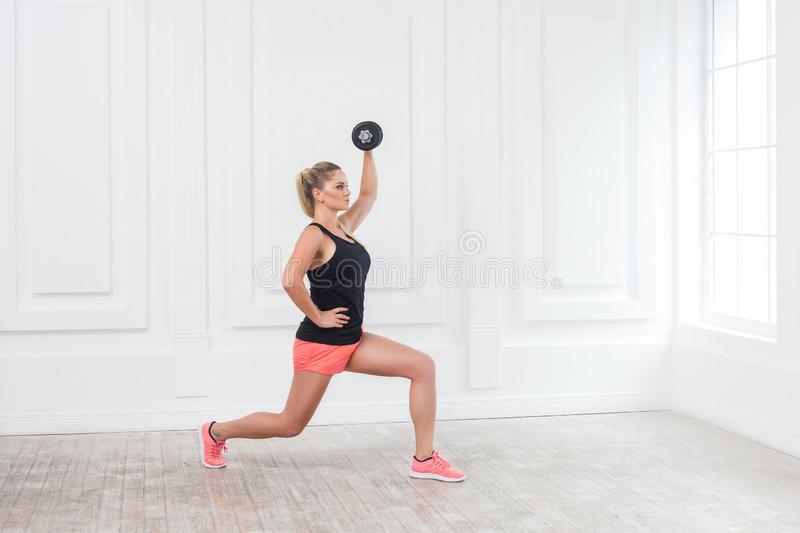 Side view portrait of young athletic beautiful bodybuilder woman in pink shorts and black top holding dumbells over head and doing. Squats with one leg at the stock photo