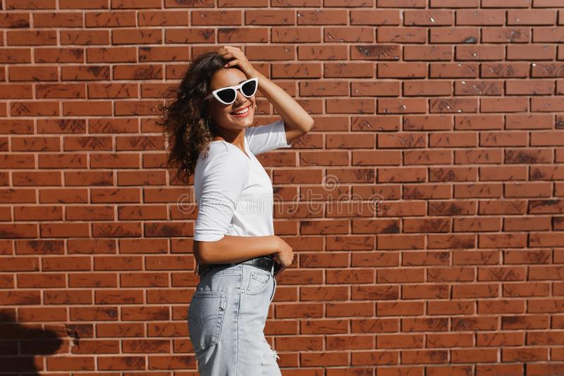 Side view portrait of young beautiful happy woman in casual cloth against brick wall royalty free stock images