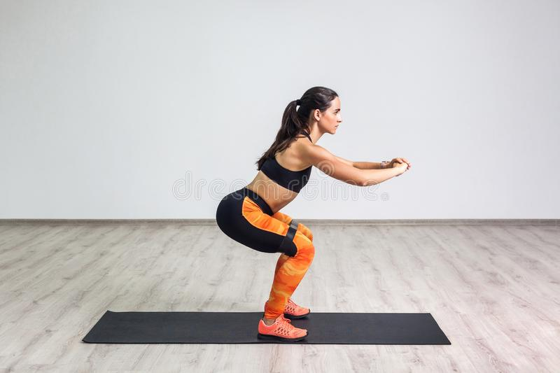 Side view portrait of young sporty healthy beautiful woman in black top and orange leggings doing squatting with elastic. Resistance band. Isolated, white wall royalty free stock photos
