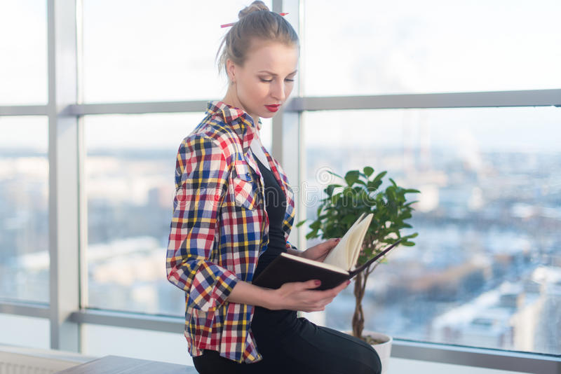 Side view portrait of young woman sitting, looking down, reading the book, learning at light room in morning with her stock photo