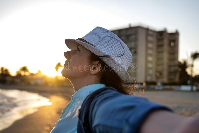 Portrait of a young woman in a white hat on the seashore enjoying vacation stock photo