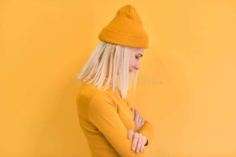 Side view of pretty blonde hair woman wears yellow clothes, hat, posing on yellow studio background. Copy space for advertisement royalty free stock image