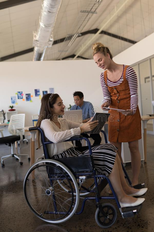 Disabled female executive discussing over digital tablet royalty free stock photos