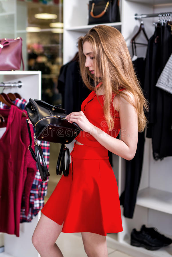 Side view of pretty girl wearing red set doing shopping alone choosing, holding, examining new bag in fashion store royalty free stock photography