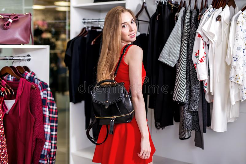Side view of pretty girl wearing red set doing shopping alone choosing, holding, examining new bag in fashion store. E view of pretty girl wearing red set doing stock photography