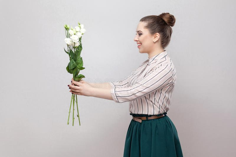Side view profile of attractive romantic young woman in striped shirt and green skirt holding bouquet of white flowers and giving stock image