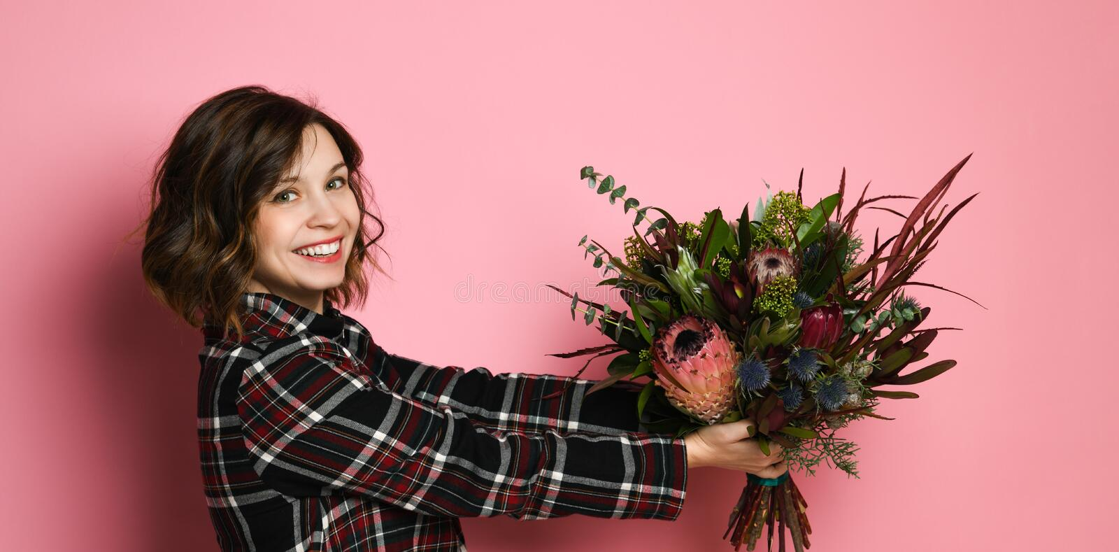 Side view profile of attractive young woman in a dark checkered dresst holding bouquet of flowers and giving you. stock image