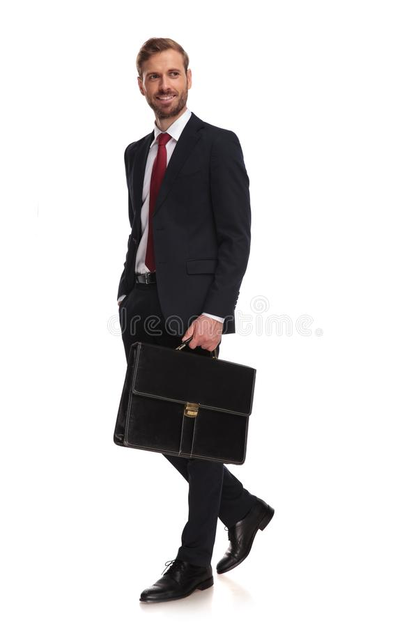 Side view of relaxed businessman with suitcase walking to work stock photography