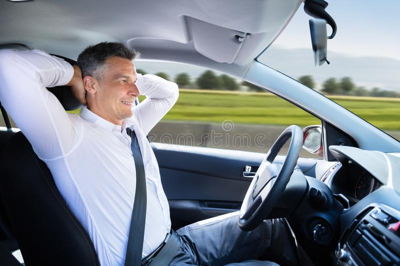 Relaxed Man Sitting In Self Driving Car. Side View Of A Relaxed Mature Man Sitting In Autonomous Self Driving Car royalty free stock photography