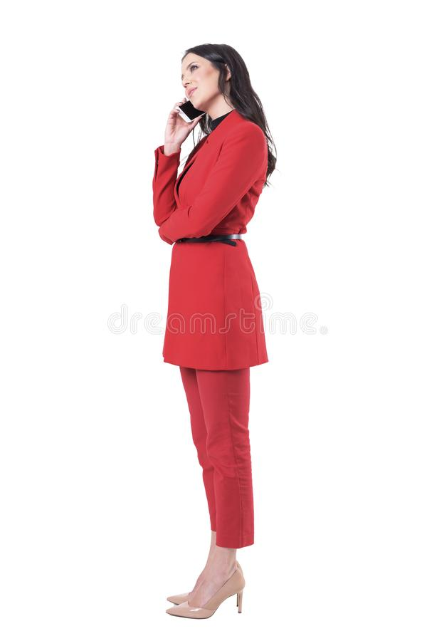 Side view of relaxed smiling corporate woman talking on the phone and looking up thoughtfully royalty free stock photo