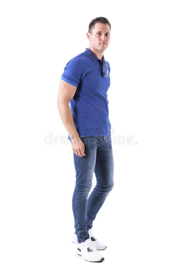 Side view of relaxed young adult casual man walking with sunglasses on neck looking at camera. royalty free stock photography