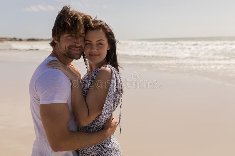 Romantic happy young couple embracing on beach stock images