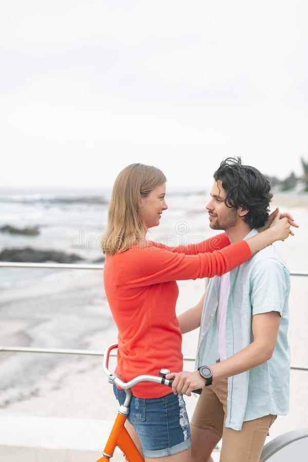 Romantic Caucasian couple embarrassing each other on cycle at beach stock photo