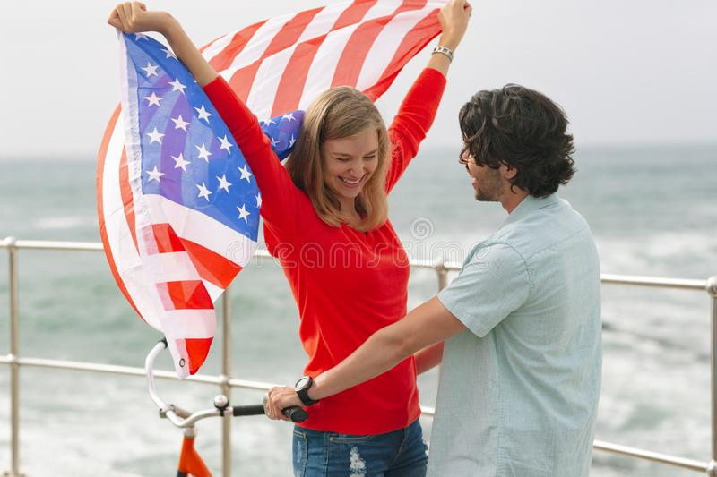 Romantic Caucasian couple standing at promenade while holding american flag stock photo