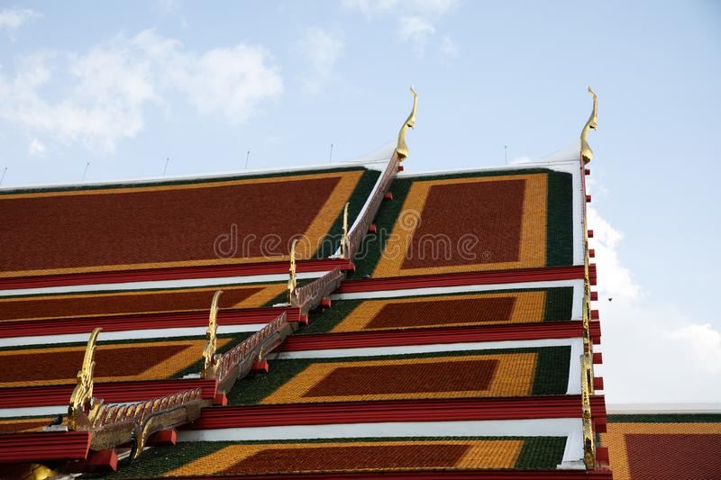 Side view of the roof of the Royal temple in Bangkok with blue and white sky stock photo