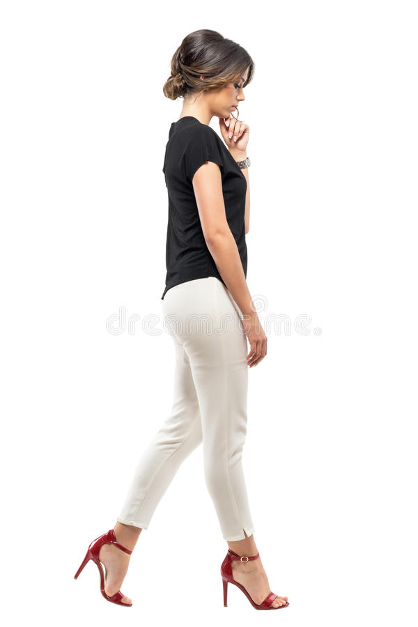 Side view of sad worried business woman in suit walking and looking down stock photo