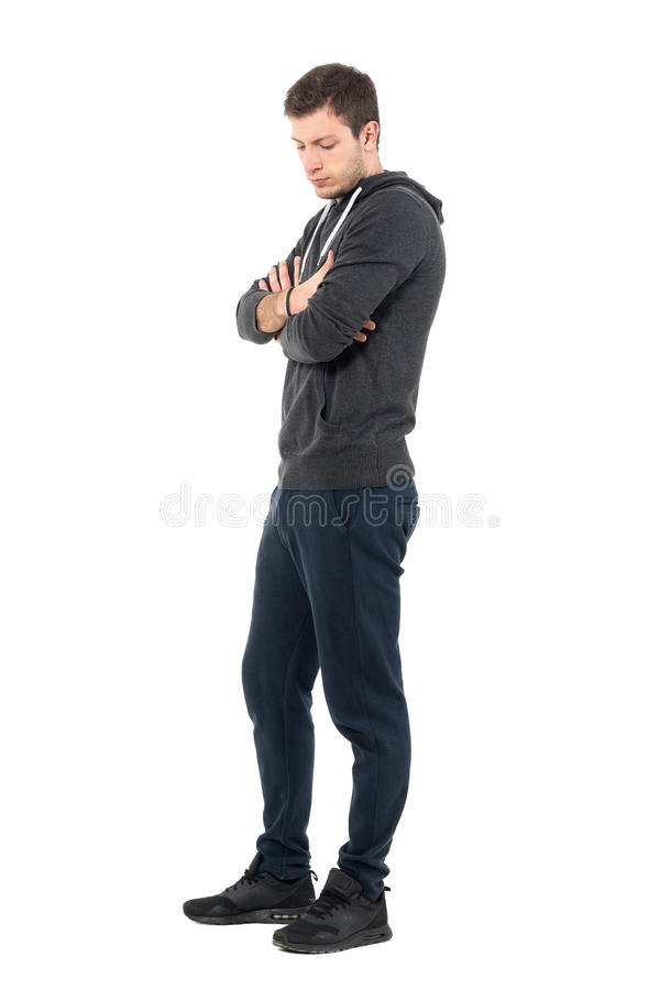Side view of sad young man in sportive clothing looking down with crossed arms royalty free stock photography