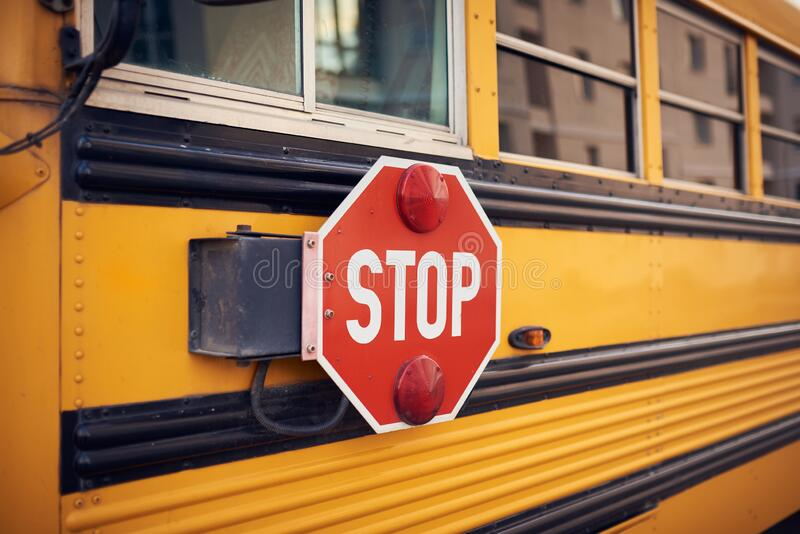 Side view of a school bus and its stop signal.  stock photo
