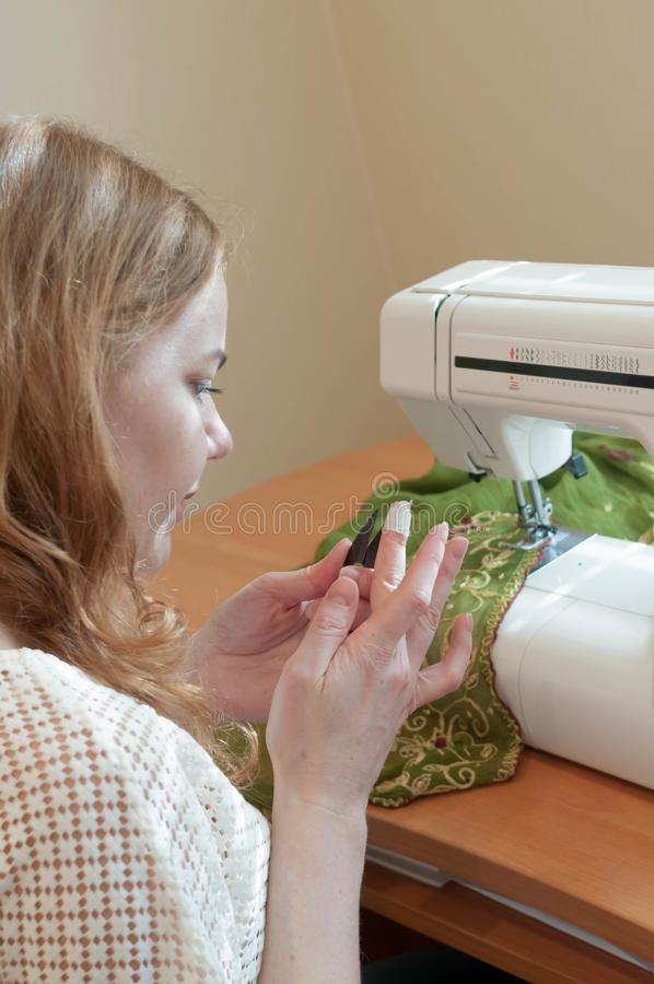 Seamstress sitting at table with sewing machine and looking at wounded finger stock photos