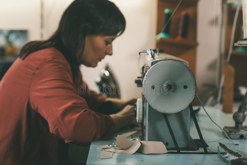 Side view of seamstress working with sewing machine and leather at shoemaker. Workshop royalty free stock photography