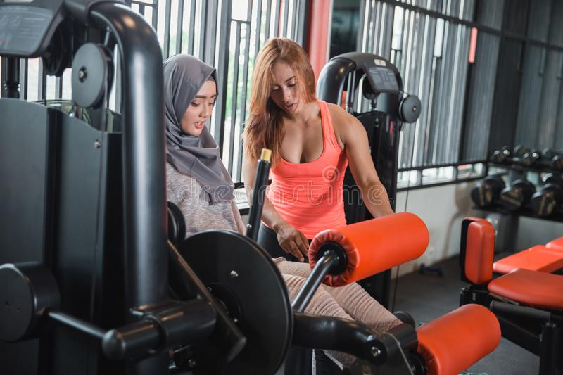 Side view seated leg curl machine exercise muslim women hijab. And personal trainer woman royalty free stock photos