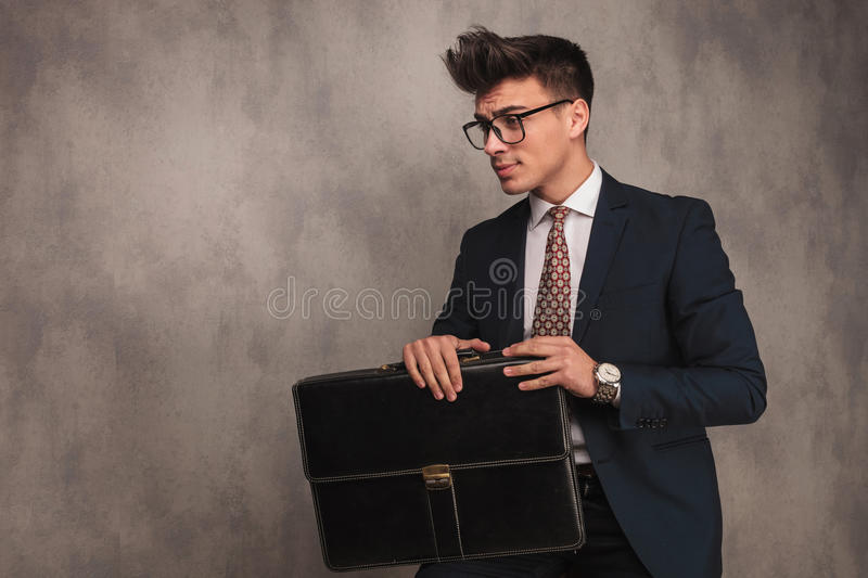 Side view of a seated young business man holding briefcase. And looking away to a side in studio royalty free stock images