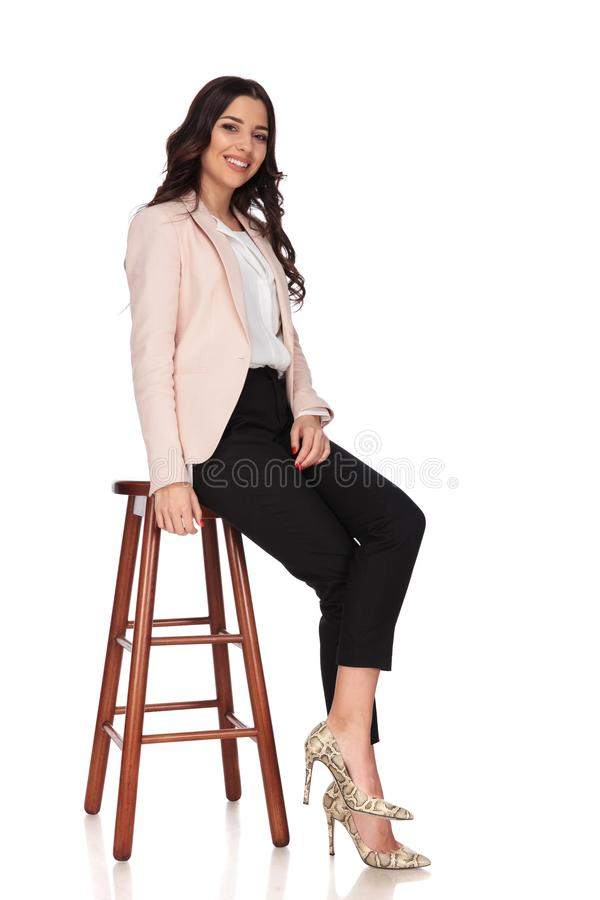 Side view of a seated young smiling business woman royalty free stock images