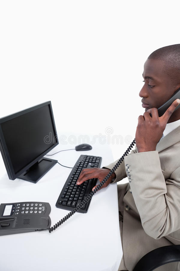 Side view of a secretary answering the phone while using a computer royalty free stock photos