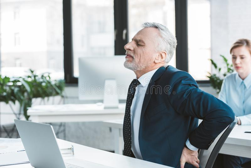 Side view of senior businessman. Suffering from pain in back while sitting at workplace stock photography