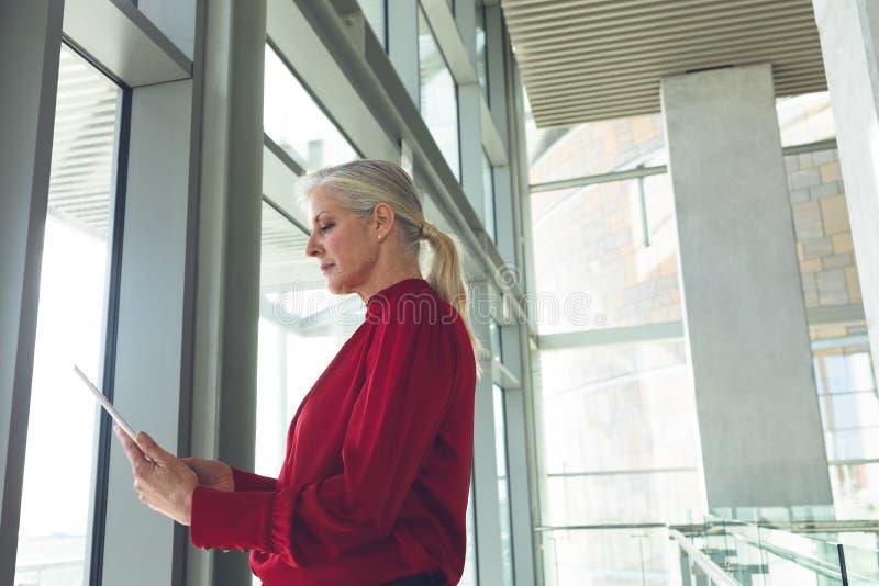 Senior businesswoman using digital tablet in office building. Side view of senior Caucasian businesswoman using digital tablet in modern office building stock images