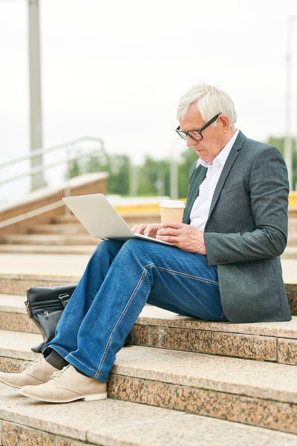Elderly businessman withhot beverage using laptop royalty free stock image