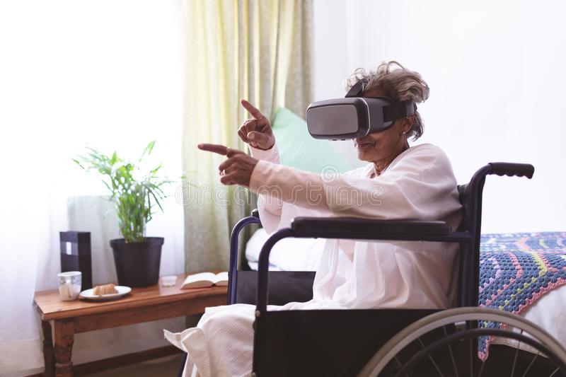 Senior woman using virtual realty headset at nursing home. Side view of senior mixed race woman using virtual realty headset in wheelchair at nursing home royalty free stock photography