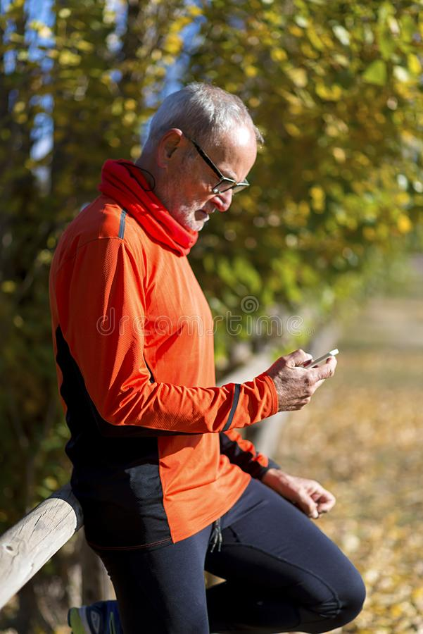 Side view of a senior runner man leaning on fence while testing exercise in a mobile phone outdoors in a sunny day.  stock photography