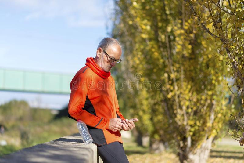 Side view of a senior runner man leaning on fence while testing exercise in a mobile phone outdoors in a sunny day.  stock image